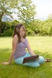 Bello adolescente sorridente con il pc della compressa, all'aperto Fotografia Stock Libera da Diritti