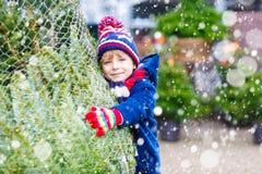 Bello albero di Natale sorridente della tenuta del ragazzino Fotografia Stock