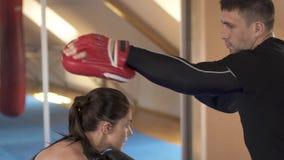 Bello allenamento castana di kickboxing della donna con un istruttore nella palestra di forma fisica Movimento lento Forte e donn stock footage