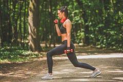 Bello allenamento della sportiva utilizzando i piccoli pesi nella natura Immagine Stock