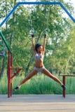 Bello allenamento di forma fisica della donna di forma fisica sugli anelli relativi alla ginnastica Immagini Stock Libere da Diritti