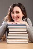 Bello allievo felice che si siede con i libri di studio Fotografia Stock