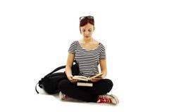 Bello allievo femminile che si siede sullo studio del pavimento Fotografie Stock