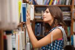 Bello allievo femminile in una libreria Immagine Stock