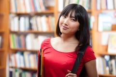 Bello allievo femminile in una libreria Immagini Stock