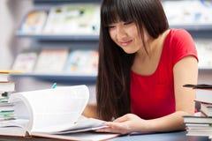 Bello allievo femminile in una libreria Fotografie Stock Libere da Diritti