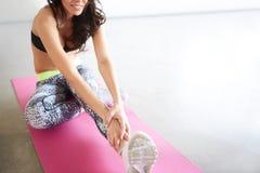 Bello allungamento femminile irriconoscibile sul pavimento Fotografia Stock