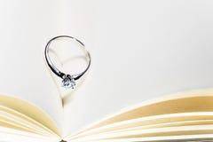 Bello anello di diamante sul libro aperto in bianco con lo shado di forma del cuore Fotografia Stock Libera da Diritti