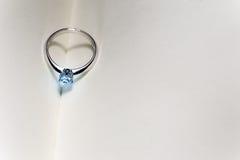 Bello anello di diamante sul libro aperto in bianco con lo shado di forma del cuore Fotografie Stock