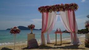 Bello arco di nozze con i fiori sulla spiaggia video d archivio