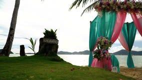 Bello arco di nozze con i fiori sulla spiaggia fra le palme archivi video
