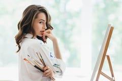 Bello artista della donna con le spazzole che posano nel suo studio immagini stock libere da diritti