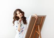 Bello artista felice della donna che posa nello studio con il suo materiale illustrativo fotografia stock