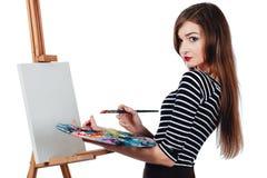 Bello artista sveglio della ragazza che dipinge un'immagine sul cavalletto della tela Spazio per testo Fondo bianco dello studio, Immagini Stock Libere da Diritti
