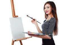 Bello artista sveglio della ragazza che dipinge un'immagine sul cavalletto della tela Spazio per testo Fondo bianco dello studio, Immagine Stock Libera da Diritti
