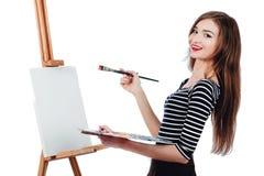 Bello artista sveglio della ragazza che dipinge un'immagine sul cavalletto della tela Spazio per testo Fondo bianco dello studio, Fotografie Stock