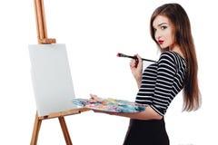 Bello artista sveglio della ragazza che dipinge un'immagine sul cavalletto della tela Spazio per testo Fondo bianco dello studio, Fotografia Stock