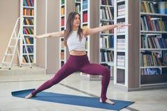 Bello asana adatto sportivo Virabhadrasana 2 di yoga di pratiche della donna di yogini - posa 2 del guerriero nella biblioteca fotografia stock libera da diritti