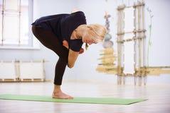 Bello asana sportivo di torsione di yoga di pratiche della donna degli Yogi di misura nella stanza di forma fisica Immagini Stock Libere da Diritti