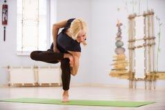 Bello asana sportivo di torsione di yoga di pratiche della donna degli Yogi di misura nella stanza di forma fisica Fotografia Stock Libera da Diritti