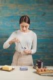 Bello asiatico che sorride mentre assaggiando i suoi muffin casalinghi fotografia stock libera da diritti