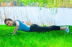 Bello atleta della donna addetto agli sport sulla via, in un parco, addestramento di conduzione alle teste di legno in sue mani Fotografie Stock