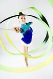 Bello atleta della ginnasta che fa esercizio con il nastro O isolata Fotografia Stock