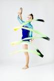 Bello atleta della ginnasta che fa esercizio con il nastro O isolata Immagine Stock Libera da Diritti