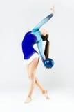 Bello atleta della ginnasta che fa esercizio con la palla isolato sopra Fotografia Stock
