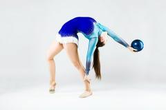 Bello atleta della ginnasta che fa esercizio con la palla isolato sopra Immagine Stock Libera da Diritti