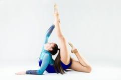 Bello atleta della ginnasta che fa esercizio Isolato su bianco Immagini Stock