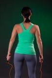 Bello atletico, condizione della donna di forma fisica, posante con una corda di salto su un fondo grigio con una lampadina verde Fotografia Stock