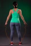 Bello atletico, condizione della donna di forma fisica, posante con una corda di salto su un fondo grigio con una lampadina verde Immagini Stock Libere da Diritti