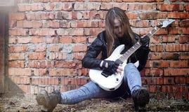 Bello attuatore della ragazza con la chitarra elettrica Un musicia della roccia Fotografia Stock