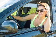 Bello autista femminile che sorride mentre conducendo la sua automobile immagini stock libere da diritti