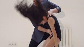 Bello bachata di dancing delle coppie nella stanza bianca video d archivio
