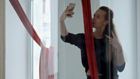 Bello ballerino che prende selfie facendo uso dello smartphone con seta aerea dopo l'allenamento Immagini Stock Libere da Diritti