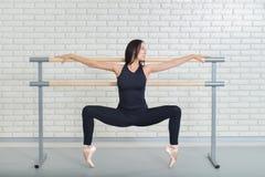 Bello ballerino di balletto che pratica vicino alla sbarra allo studio di balletto, ritratto integrale della ballerina Fotografia Stock Libera da Diritti