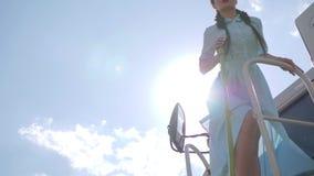 Bello ballo della ragazza nel vestito sulla associazione-mietitrice in lampadina sul cielo blu del fondo video d archivio