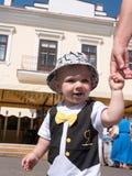 Bello bambino che cammina con sua madre su una festa della città Farfalla e cappuccio alla moda vestiti del bambino Immagini Stock Libere da Diritti