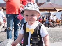Bello bambino che cammina con sua madre su una festa della città Farfalla e cappuccio alla moda vestiti del bambino Fotografia Stock