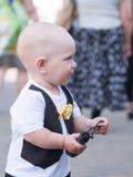 Bello bambino che cammina con sua madre su una festa della città Farfalla e cappuccio alla moda vestiti del bambino Tenuta del ra Fotografia Stock