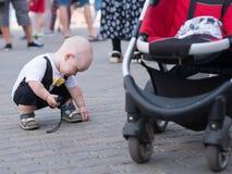 Bello bambino che cammina con sua madre su una festa della città Farfalla e cappuccio alla moda vestiti del bambino Tenuta del ra Immagine Stock