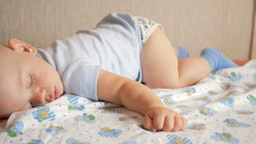 Bello bambino che dorme nella posa divertente su un letto Sotto il pannolino del bambino, il ragazzo circa un anno video d archivio