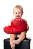Bello bambino che si siede con il cuscino a forma di del cuore Fotografie Stock