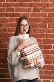 Bello bere della ragazza caffè--va sui libri Fotografie Stock Libere da Diritti