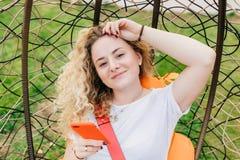 Bello blogger femminile contentissimo con capelli leggeri ricci, Smart Phone di usi per l'invio dei nuovi posti di lavoro sul suo fotografia stock