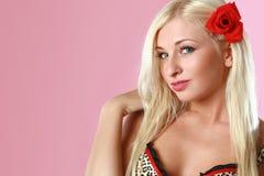 Bello blonde sexy con il fiore rosso in capelli Fotografia Stock