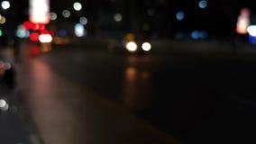 Bello bokeh variopinto delle automobili e delle vie della città alla notte archivi video