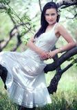 Bello brunette che si siede sulla filiale Fotografia Stock Libera da Diritti